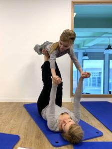 Une maman et sa fille en posture de yoga
